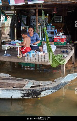 Little boy doing shool homework with his mother in House on stilts, Kompong Chhnang, Cambodia - Stock Photo