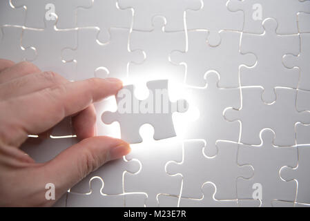 jigsaw puzzle piece with light glow, business concept for completing the final puzzle piece - Stock Photo