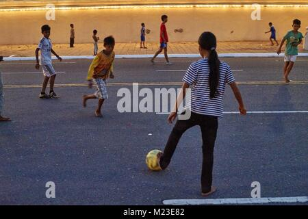 Cambodian girl and Children on floating house, Kompong Chhnang, Cambodia playing football in front of Royal Palace, - Stock Photo