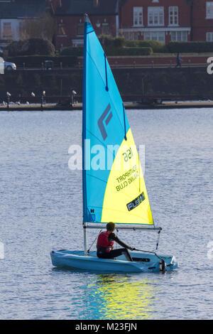 A man sailing a single seat sail boat on Marine boating lake in Southport Merseyside, UK. - Stock Photo