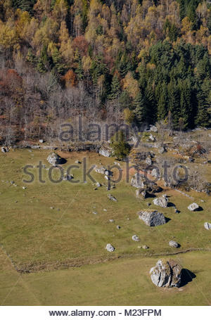 Fallen rocks, pasture and forest in fall in the french Pyrenees mountains - Stock Photo