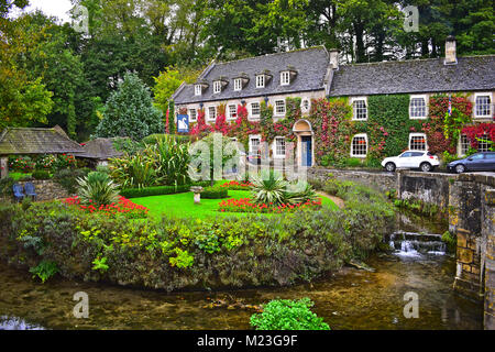 The Swan Hotel in Bibury, a picturesque Cotswold village. The stone bridge is crossing the river Coln. - Stock Photo