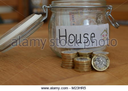 Class jar with house written on white label with currency notes inside and new one pound coins stacked in front. - Stock Photo