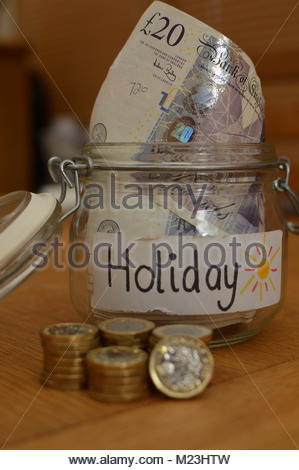 New one pound coins stacked in front of glass jar with holiday written on white label with money notes inside. - Stock Photo