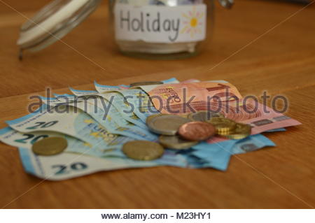 Closeup of Euro currency bank notes and coins piled on wooden table with glass savings jar in background with Holiday - Stock Photo
