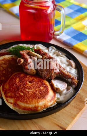 Fried in oven rabbit with fritters and onion sauce. Cast iron pan on wooden cutting board and glass with cranberry - Stock Photo