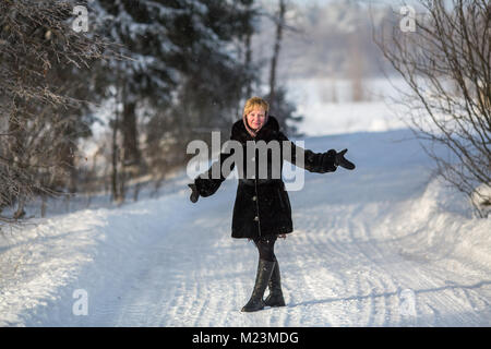 Young woman throws up his hands standing on the trail in the winter at the snowy park. - Stock Photo