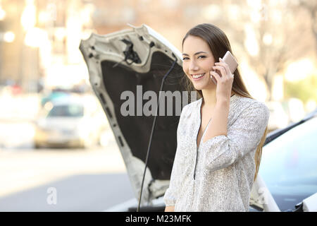 Happy driver calling insurance about a car breakdown and looking at you on the street - Stock Photo
