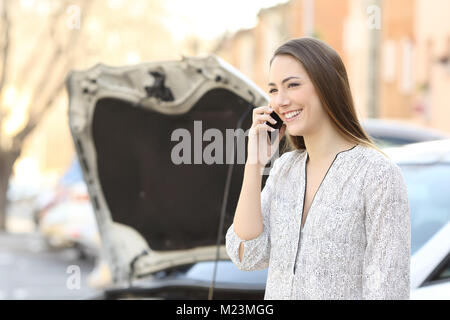 Portrait of a smiley driver calling insurance after car breakdown on the street - Stock Photo