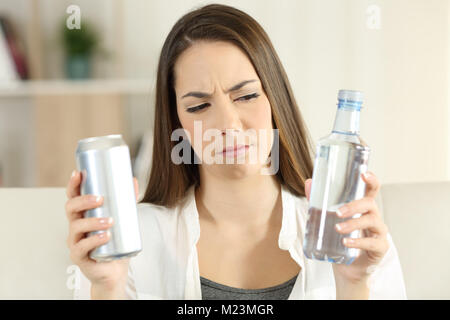 Front view portrait of a pensive woman doubting between soda drink and water at home - Stock Photo