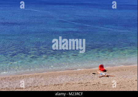 Mum with a baby in stroller lyuing on the beach, Montenegro - Stock Photo
