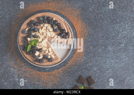 Raw vegan chocolate-caramel cheesecake with blueberries, raw candy balls and almonds. Healthy vegan food concept. - Stock Photo