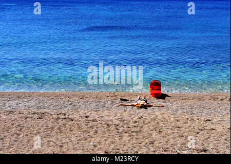 Mom with a baby in carriage on the beach - Stock Photo