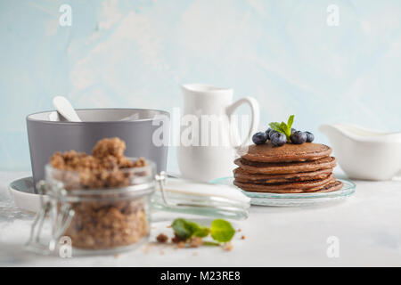 Chocolate pancakes, chocolate baked granola in a jar and milk. Healthy breakfast concept. - Stock Photo