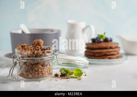 Chocolate baked granola in a glass jar. Healthy breakfast concept. - Stock Photo