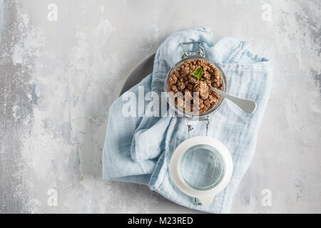 Chocolate baked granola (muesli) in a glass jar. Top view, copy space, gray background. - Stock Photo