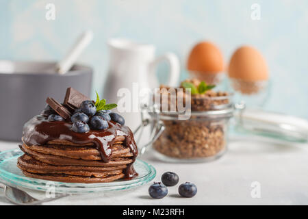 Chocolate pancakes with syrup and berries, chocolate granola, milk and eggs. Breakfast concept - Stock Photo