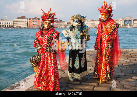 Venice, Veneto, Italy 4th February 2018. Three people wearing colourful historical costumes  and masks posing at - Stock Photo