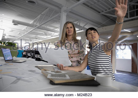 Architects with blueprints planning in office - Stock Photo