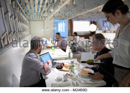 Waitress pouring wine for businessmen meeting, using laptop at working lunch in restaurant - Stock Photo