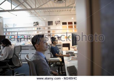 Focused designer using computer in creative open office - Stock Photo