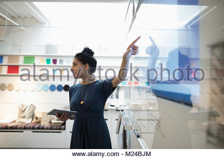 Designer with digital tablet leading meeting at screen in creative office - Stock Photo