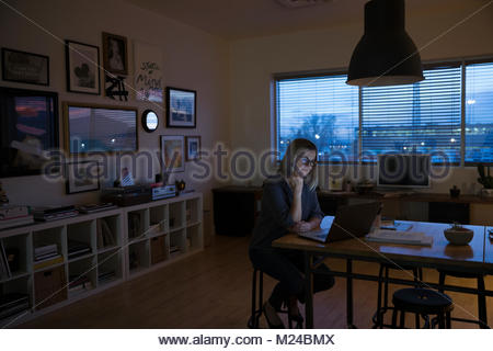 Senior woman working late at laptop in studio office - Stock Photo