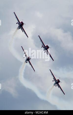 The Blades, British Civilian Aerobatic Team. Flying in Formation with White Smoke On. 4 Extra 300LPs Displaying - Stock Photo