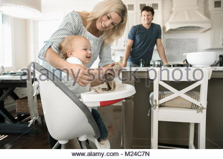 Mother wiping hands of baby son in high chair - Stock Photo