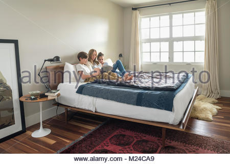 Mother and children reading book on bed - Stock Photo