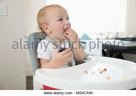 Messy baby boy eating in high chair - Stock Photo