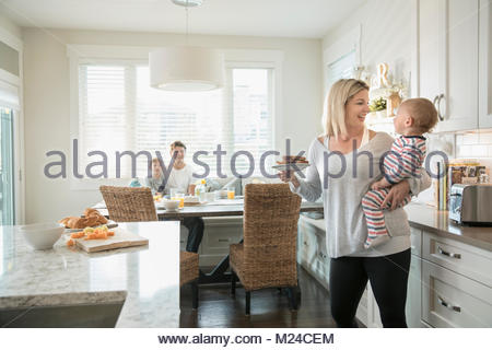 Mother eating, holding baby son in kitchen - Stock Photo