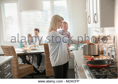 Mother cooking, holding baby son in kitchen - Stock Photo