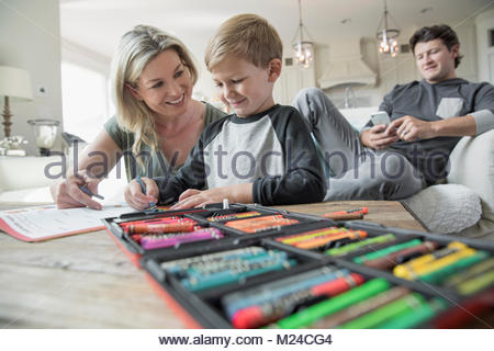 Mother and son coloring in living room - Stock Photo