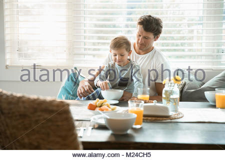 Father and son eating breakfast in breakfast nook - Stock Photo