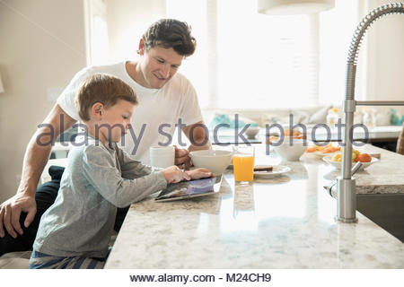 Father and son eating breakfast and using digital tablet at kitchen island - Stock Photo