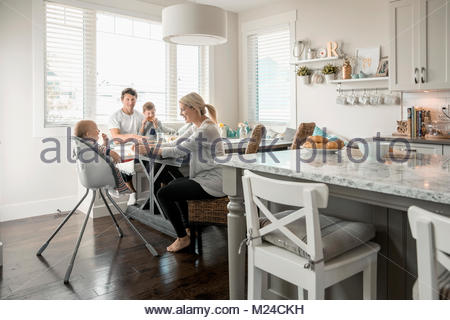 Family eating breakfast in breakfast nook - Stock Photo