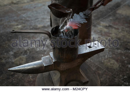 Blacksmith cooling hot metal with water over pot on anvil - Stock Photo
