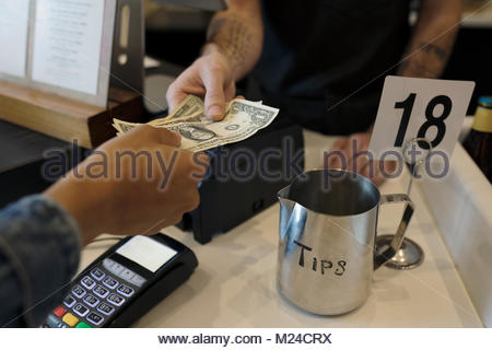 Close up customer paying cashier with cash next to tip jar - Stock Photo