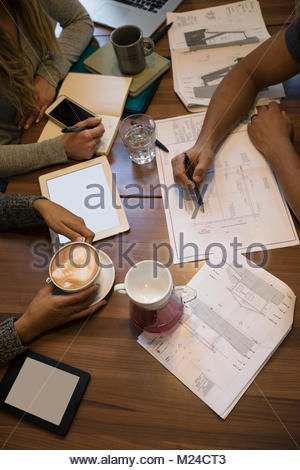 Overhead view business people drinking coffee, working, planning and discussing paperwork - Stock Photo