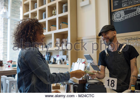 Friendly male barista taking money from female customer in cafe - Stock Photo