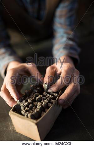 Close up blacksmith selecting tip from box - Stock Photo