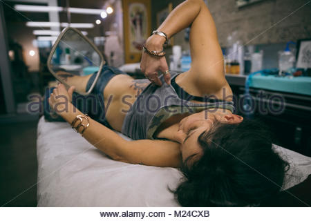 Woman with hand mirror checking out side tattoo on table in tattoo studio - Stock Photo
