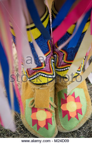 Close up vibrant, multicolor moccasins on feet of Native American Indian girl - Stock Photo