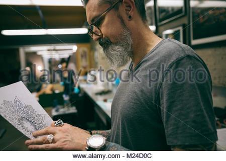 Tattoo artist reviewing sketch in tattoo studio - Stock Photo
