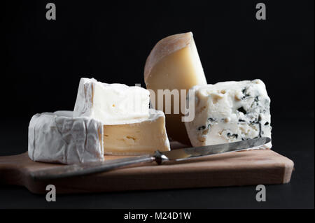 Assortment of  cheese on a wooden plate with a vintage knife. Black background. Macro image. - Stock Photo