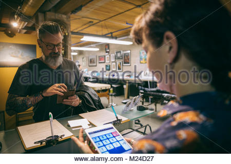 Client paying tattoo artist with digital tablet in tattoo studio - Stock Photo