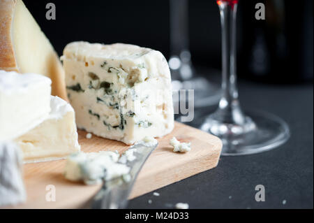 Cheese platter with piece of Roquefort cut by vintage knife and wine glasses on a backround. Black background. Macro - Stock Photo
