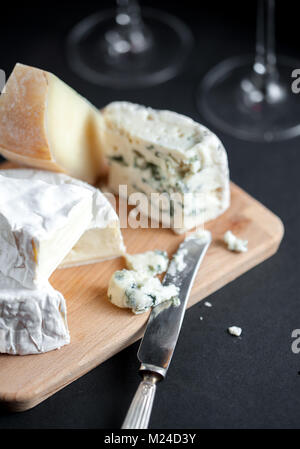 Assortment of cheeses  on a wooden plate with vintage silver knife and two wine glasses. Vertical. Macro image. - Stock Photo