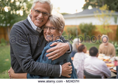 Portrait smiling, affectionate senior couple hugging at garden party lunch on patio - Stock Photo